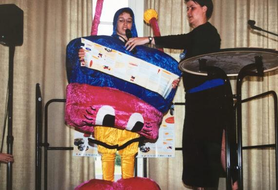 Frau im Maskottchen-Rozalla Kostüm sprichtauf Bühne