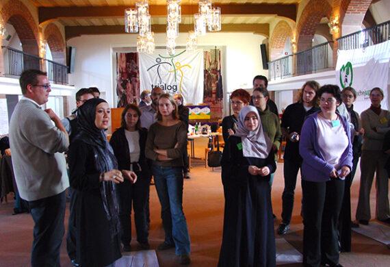 Junge Menschen muslimischen, jüdischen und christlichen Glaubens stehen diskutierendin einem raum