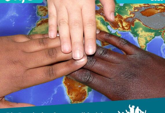 Drei KinderHände in unterschiedlichen Hutfarben liegen mit den Fingerspotzen aufeinander auf der Weltkarte über Afrika