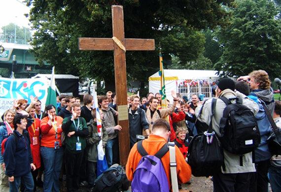 Delegation der KjG mit Kreuz und Banner vor der Zoobrücke wird von Presse fotografiert.