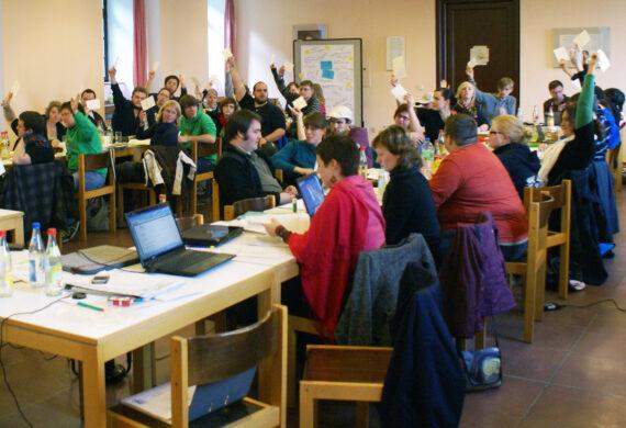 KjG Delegierte sitzen an langenTischen mit Laptop beim Bundesrat