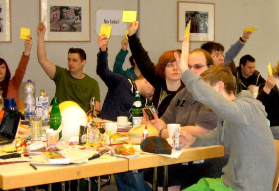 Deligierte sitzenan großem Tisch und halten gelbe Abstimmungskarten hoch