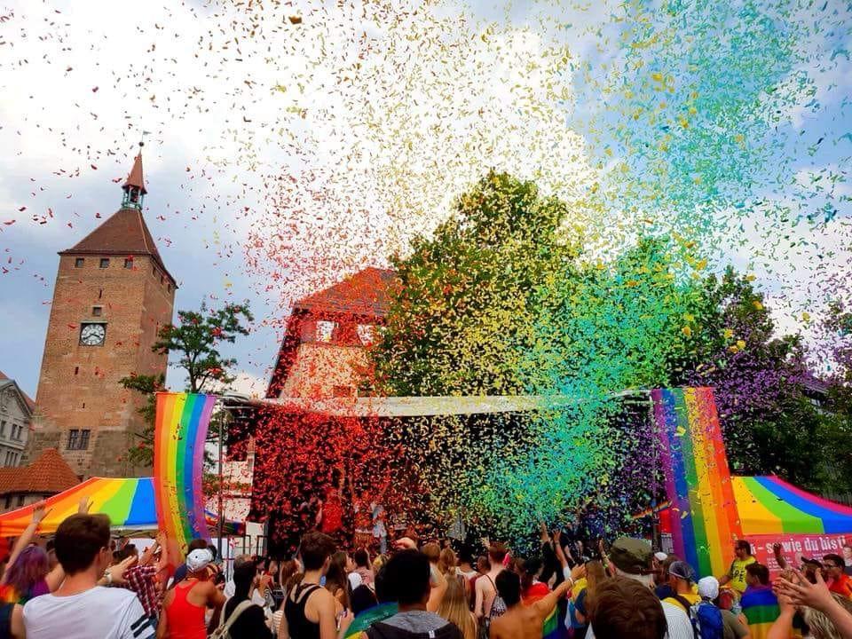 2018 Regenbogenfahnen und Confetti vor Kirchturm