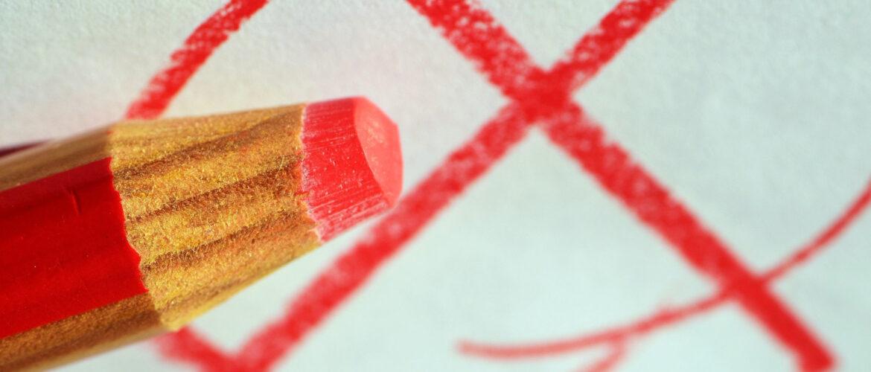 Roter Buntstift vor rotem Kreuz in rotem Kreis